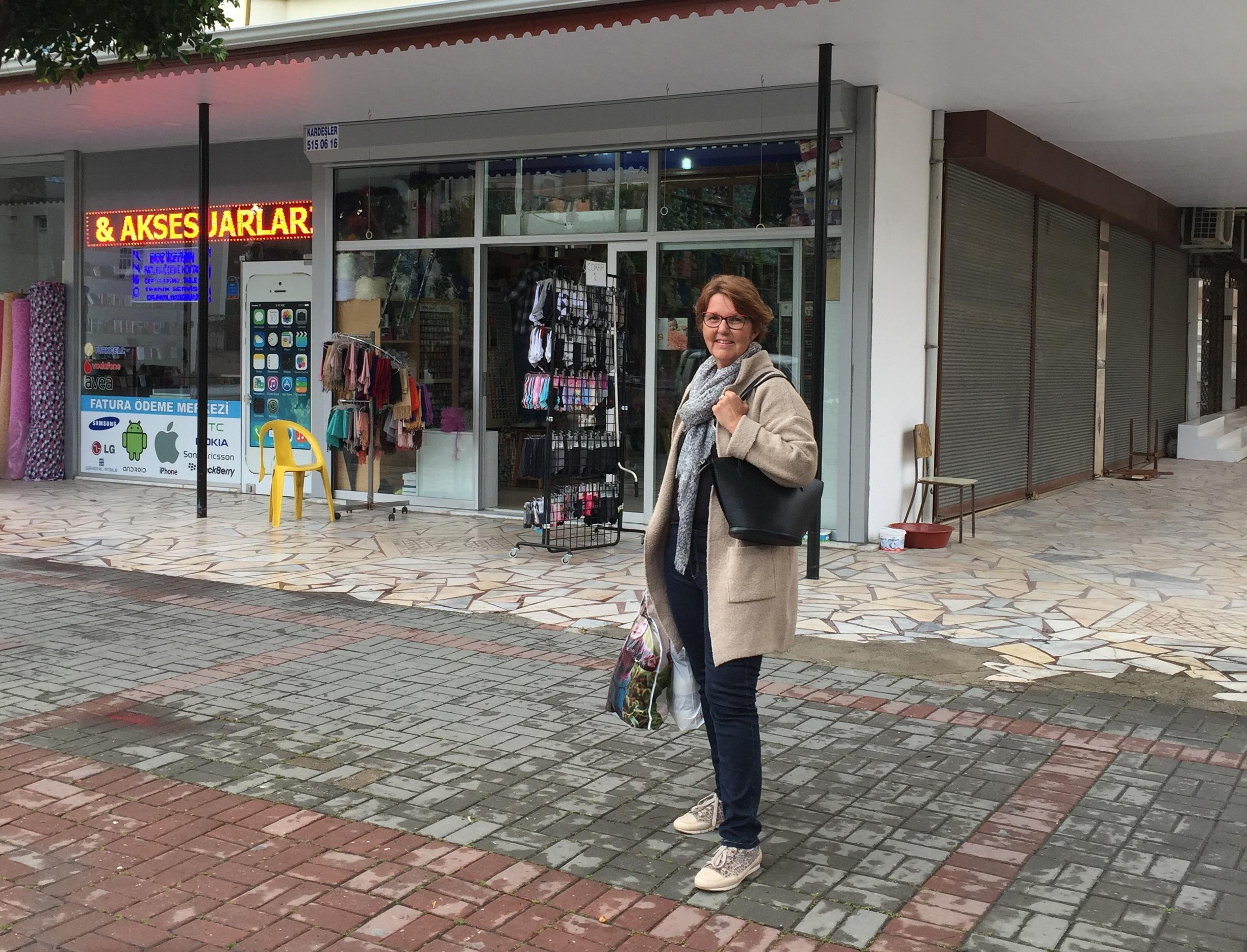 Min mor foran butikken. Lad dig ikke narre af påklædningen - billedet her er taget i efteråret. I sidste uge var vi i korte bukser og bare arme :)